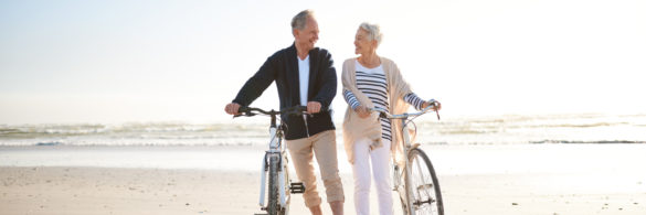An older couple stand on the beach with their bicycles.